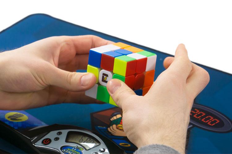 Speedcuber i färd att lösa en speedcube, en snabb Rubik's Kub, över en timer och matta.